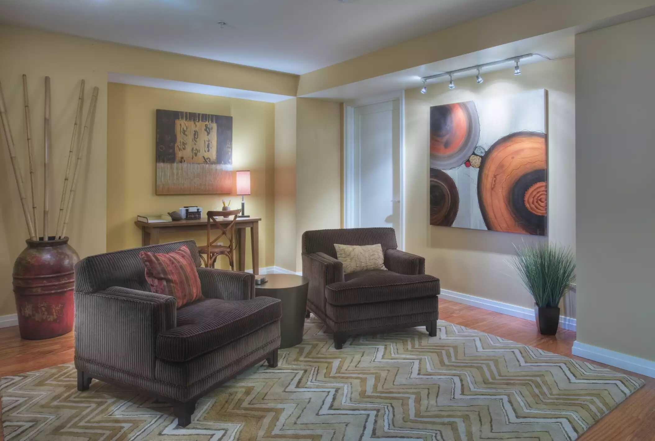 Phòng khách với đồ nội thất màu nâu, tường màu trung tính và hai bức tranh trừu tượng