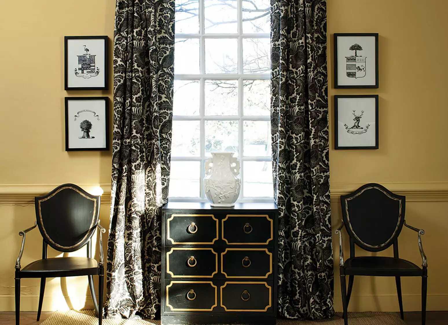 Bức tường màu vàng với đồ nội thất và rèm cửa màu đen